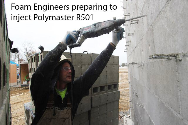 Foam Engineers preparing in inject PolyMaster R501 block fill insulation into a concrete block wall. This is at the Wentzville High School in Missouri